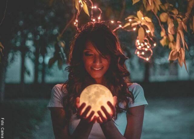Foto de una mujer con una lámpara en forma de luna entre las manos