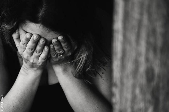 Foto de una mujer cubriendo su cara de manera triste