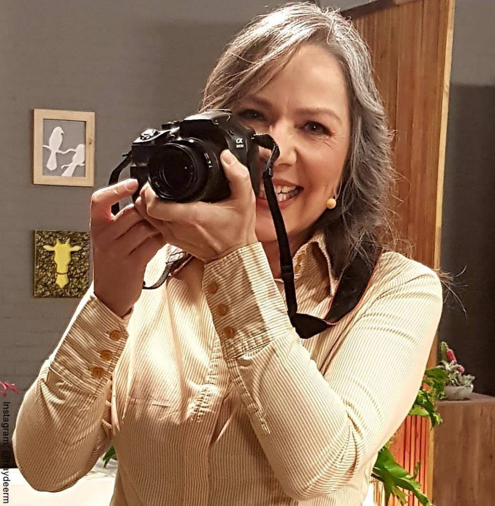 Foto de Haydée Ramírez con una cámara fotográfica en sus manos