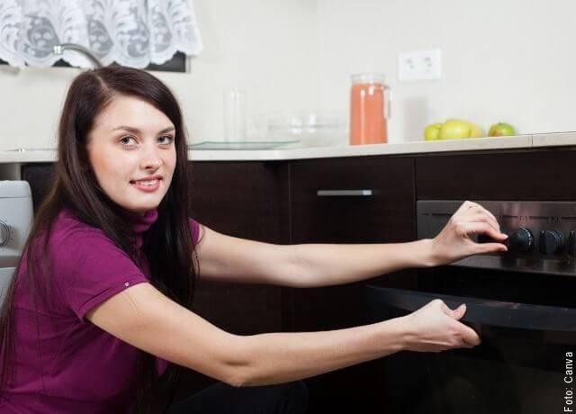 Foto de una mujer poniendo algo en el horno