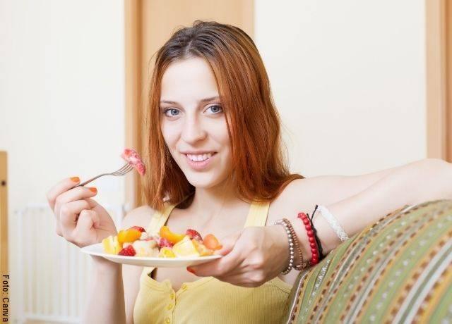 Foto de una mujer comiendo fruta