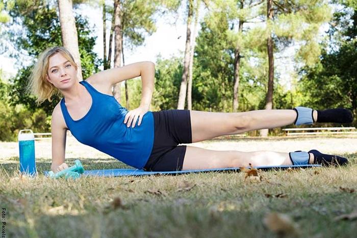 Foto de una mujer haciendo abdominales crunch laterales