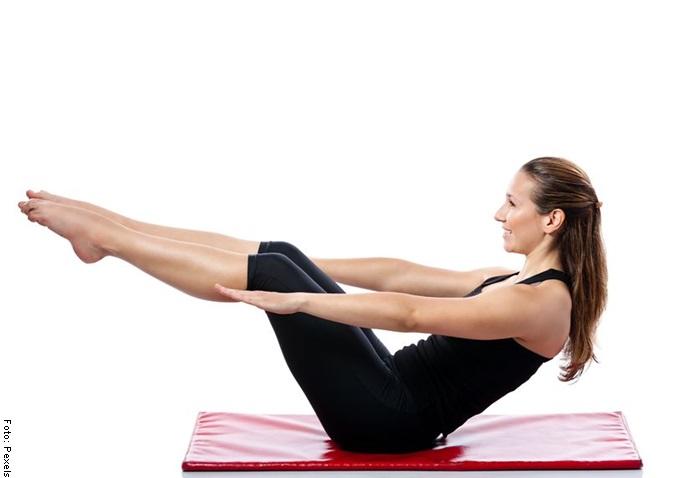 Foto de una mujer haciendo abdominales en casa con piernas elevadas