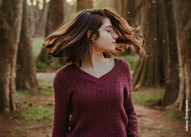 Foto de una mujer moviendo su cabeza en el bosque que muestra el aceite de ricino para el cabello