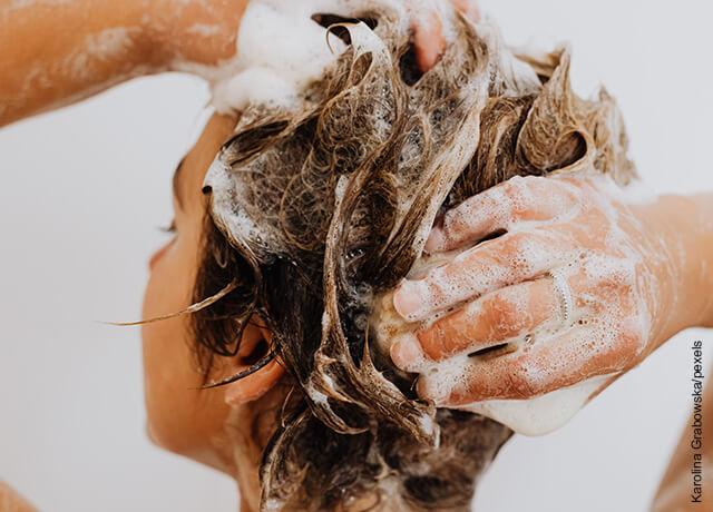 Foto de una mujer lavando su pelo con shampoo