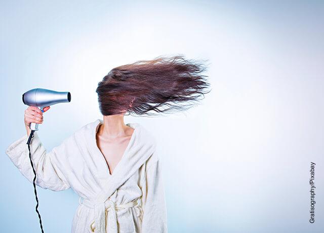 Foto de una mujer secándose el pelo