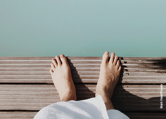 Foto de unos pies en una banca de madera