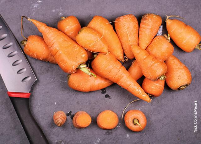 Foto de varias zanahorias sobre una tabla de picado