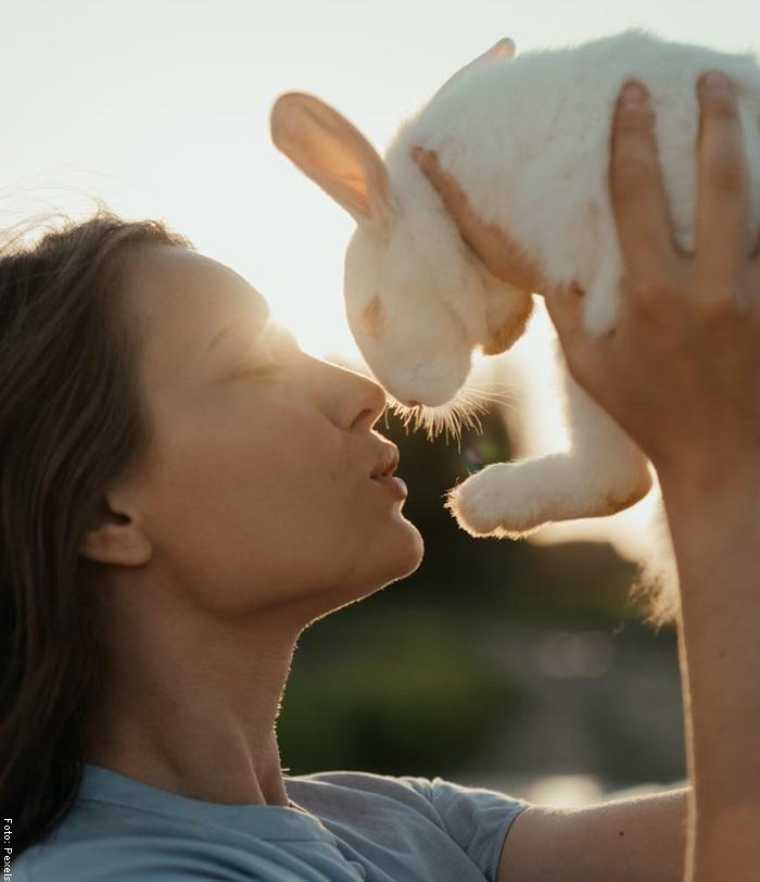 Foto de una mujer levantando un conejo