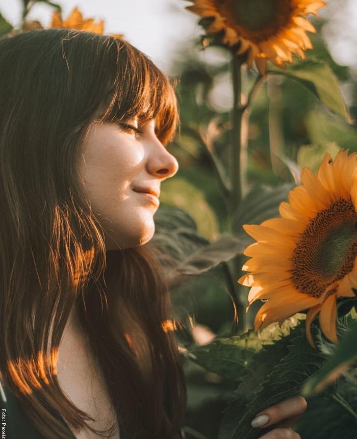 Foto de una mujer frente a unos girasoles