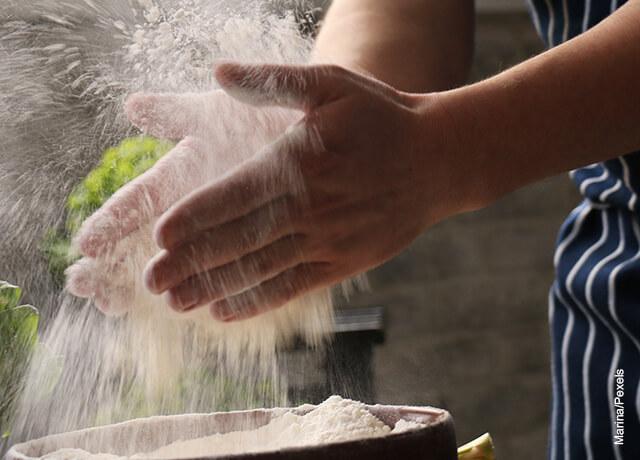 Foto de las manos de un hombre lanzando harina