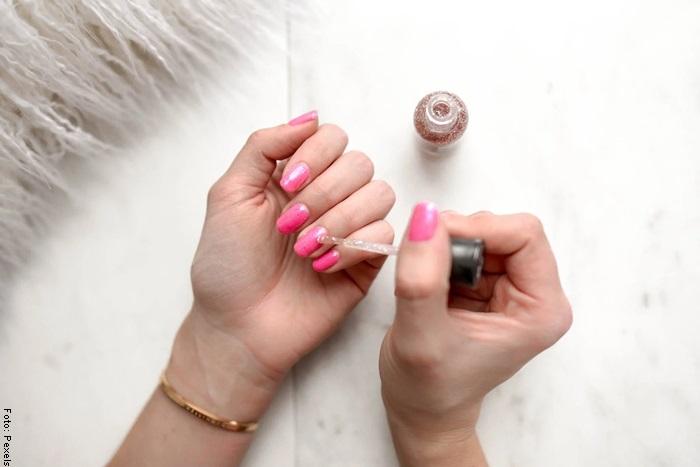Foto de una mujer aplicando esmalte para ilustrar cómo hacer crecer las uñas