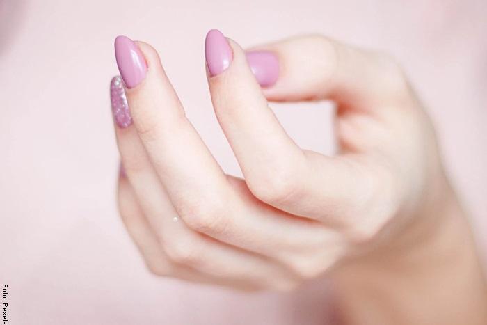 Foto de una mano con las uñas pintadas de rosa