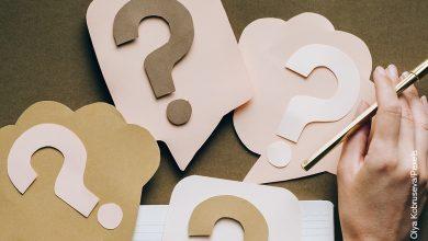 Foto de unos signos de interrogación sobre una mesa que muestran cómo hacer una cartelera