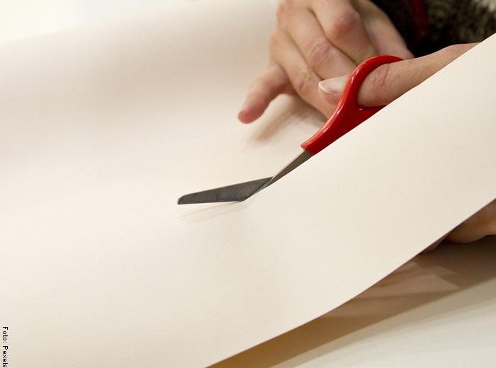 Foto de una mano cortando cartulina para ilustrar cómo hacer un gorro de chef