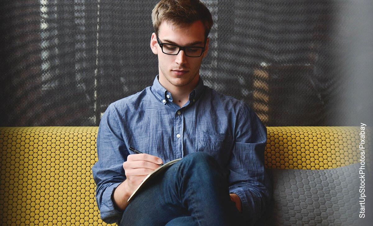 Foto de un hombre sentado en un sillón escribiendo