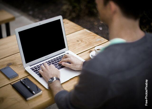 Foto de un hombre digitando en su computador que ilustra cómo hacer un informe de laboratorio