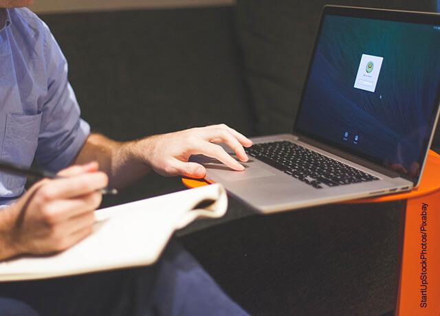 Foto de un hombre escribiendo en su computador