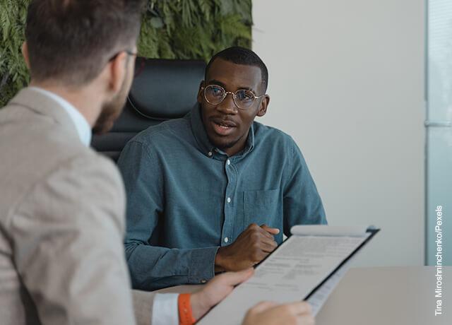 Foto de un hombre respondiendo una pregunta que muestra cómo hacer una entrevista