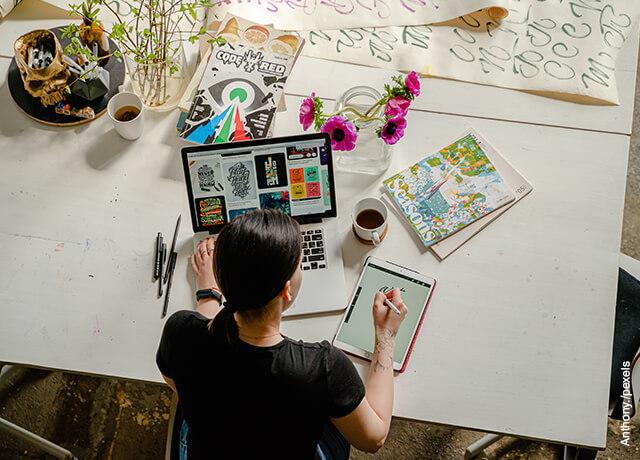 Foto de una mujer sentada frente a un computador que muestra cómo hacer una portada de un trabajo escrito