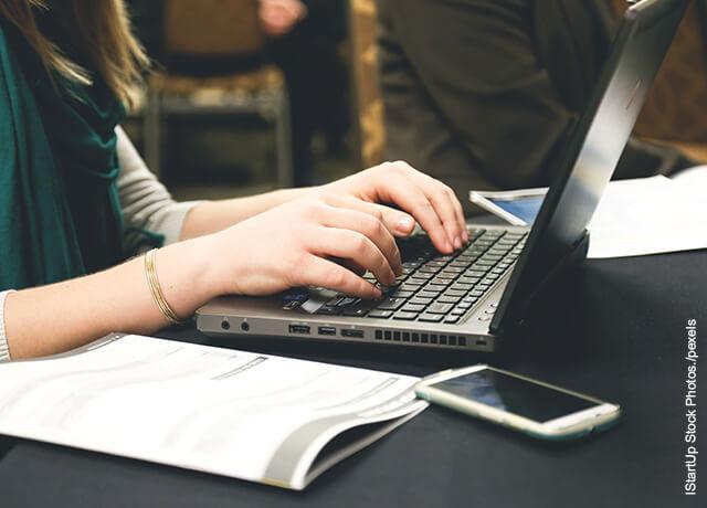 Foto de las manos de una mujer escribiendo en un computador