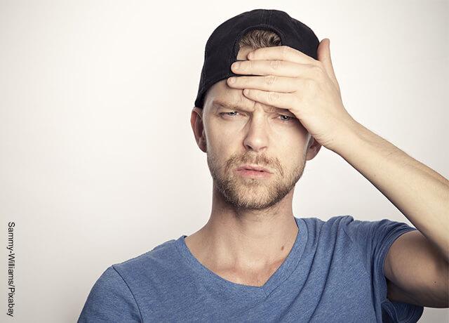 Foto de hombre tomándose la cabeza preocupado