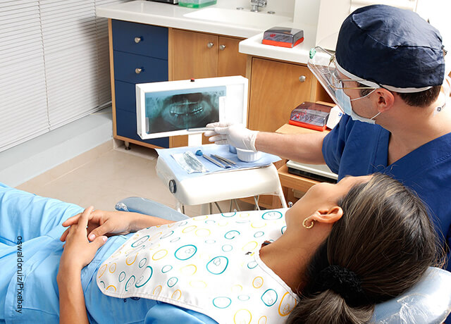 Foto de un odontólogo revisando a una paciente