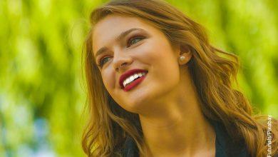 Foto de una mujer rubia sonriente que muestra el cuidado dental