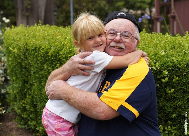 Foto de anciano abrazando a su nieta que muestra los cuidados del adulto mayor