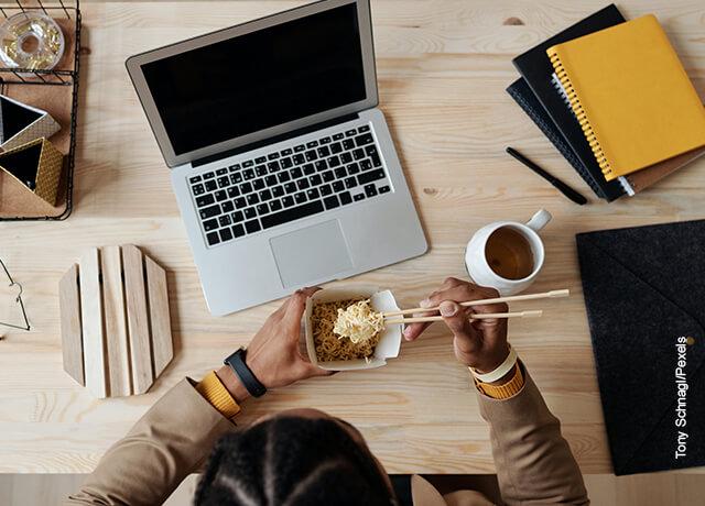 Foto de una mujer cenando frente a su computador