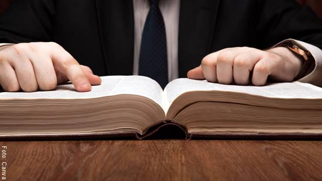 Foto de un hombre consultando el diccionario como uno de los ejemplos de palabras homófonas