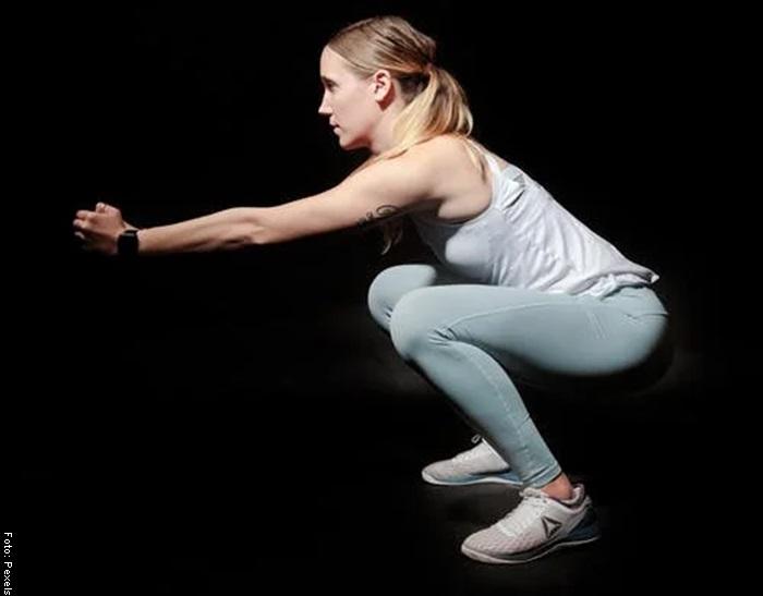 Foto de una mujer haciendo sentadillas para ilustrar ejercicios de cardio en casa