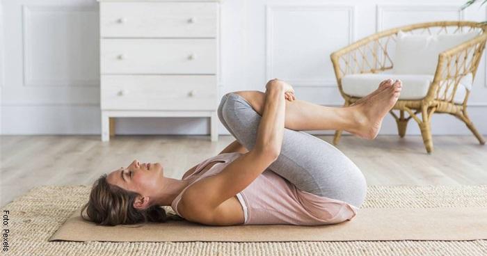 Foto de mujer haciendo el ejercicio rodillas al pecho para ilustrar los ejercicios en casa