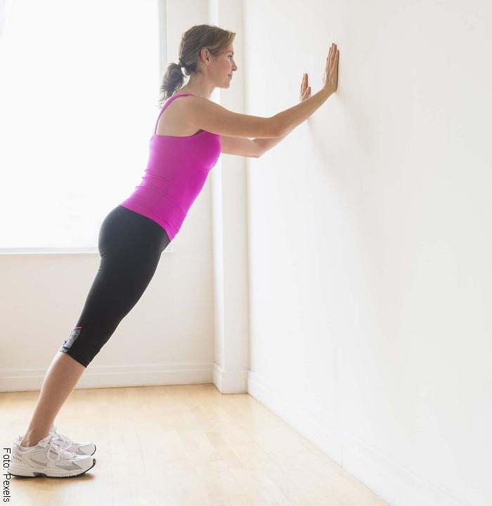 Foto de mujer haciendo flexiones contra la pared para ilustrar los ejercicios en casa