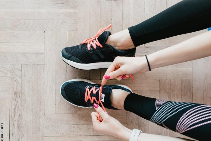 Foto de una mujer atando los cordones de unos zapatos deportivos