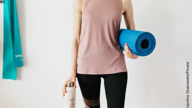 Foto de mujer sosteniendo un mat de yoga