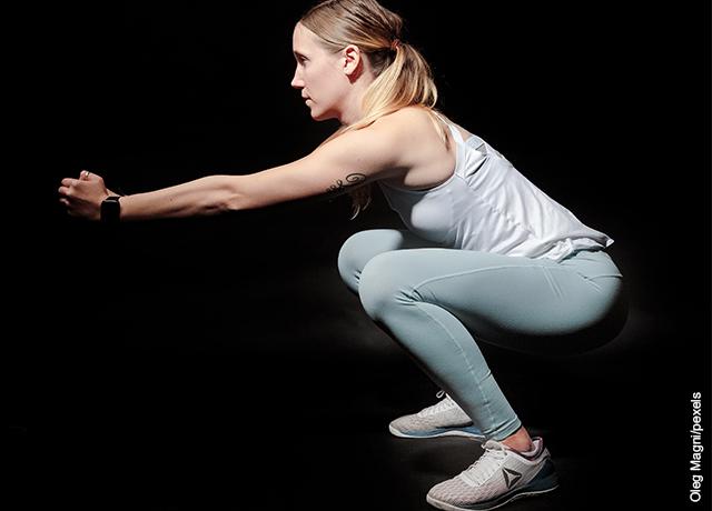 Foto de mujer haciendo sentadillas que muestra ejercicios para bajar de peso en casa