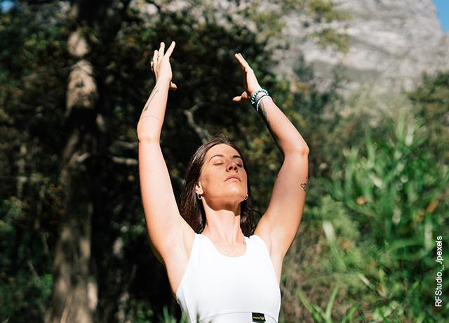 Foto de mujer elevando sus brazos en la naturaleza