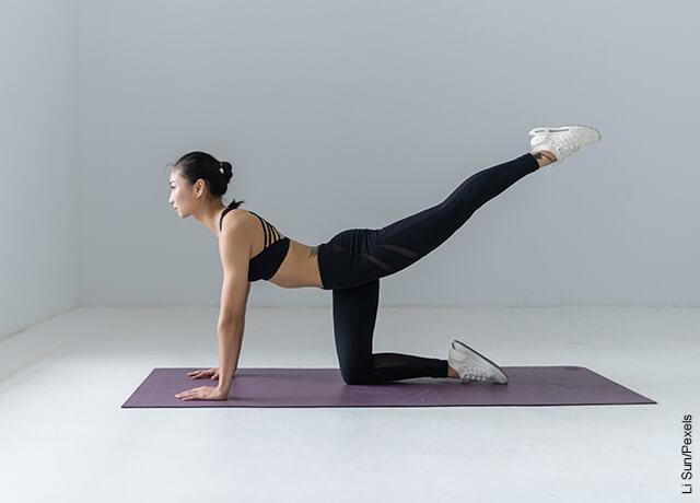 Foto de mujer levantando sus piernas haciendo ejercicio