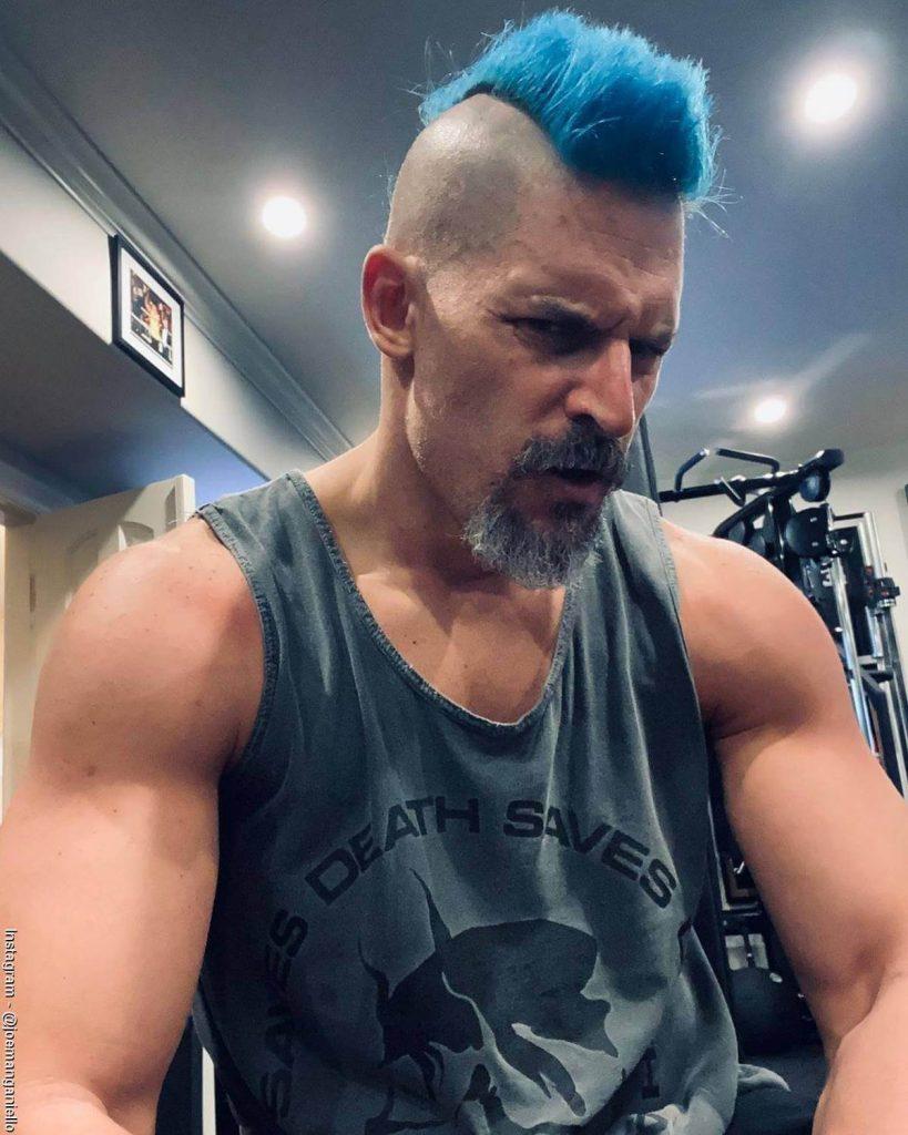 Foto de Joe Manganiello con un corte de pelo Mohicano de color azul en el gimnasio