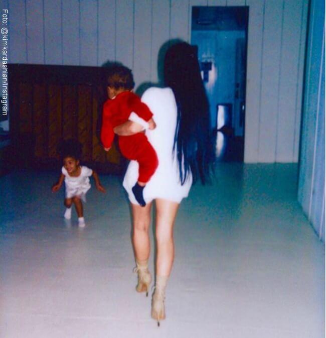 Kim Kardashian caminando con su hijo menos en brazos con una camisa blanca larga