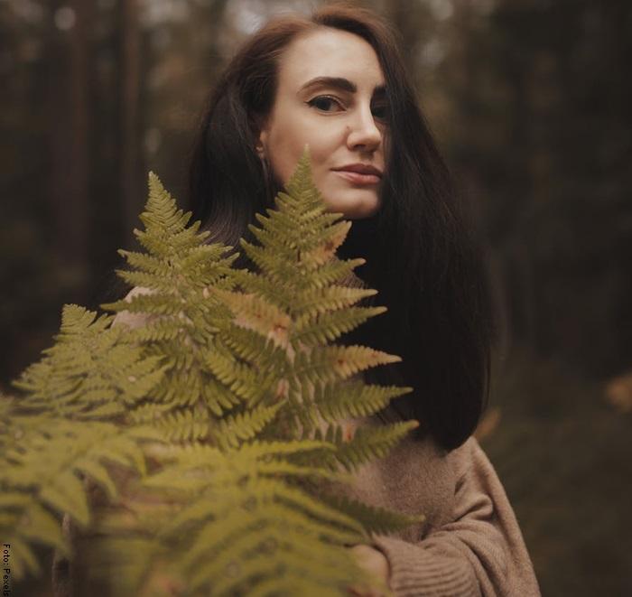 Foto de una mujer sosteniendo un helecho