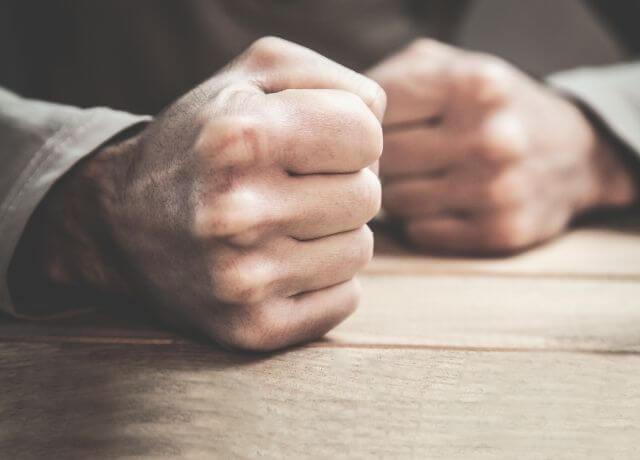 Foto de unos puños cerrados sobre una mesa