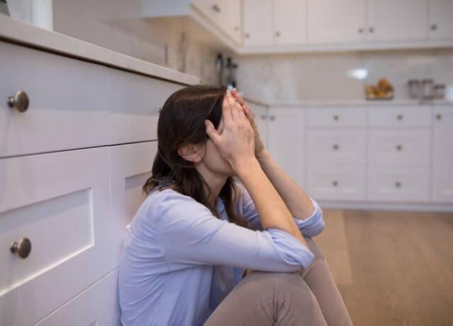 Foto de una mujer sentada en el piso tapándose el rostro con las manos