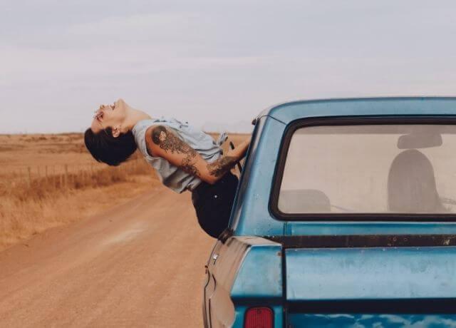 Foto de una mujer saliendo por la ventana de un carro en movimiento