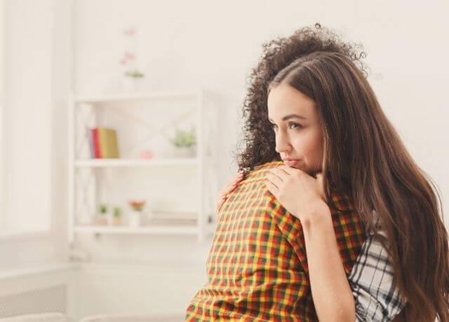 Foto de dos personas abrazadas y una tiene cara posesiva