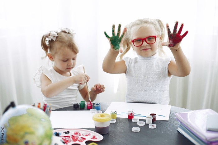 Foto de unas niñas dibujando con pinturas