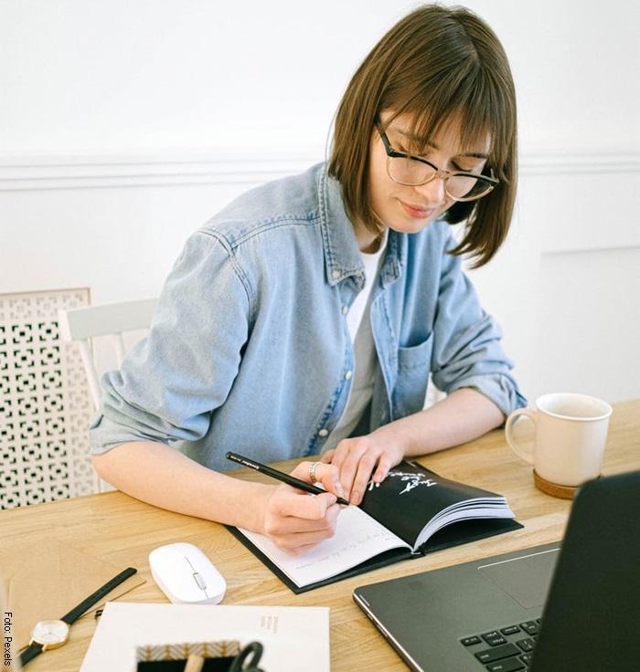 Foto de una mujer escribiendo en una libreta