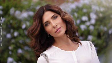 Foto de Lorena Meritano sonriendo en un jardín de flores luciendo una blusa blanca