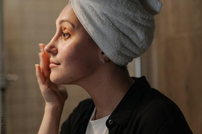 Foto de una mujer aplicándose mascarilla de aceite de oliva